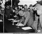 Lt. Gen. Toshimoto Hoshimo, flanked by Japanese officials, signing surrender papers.