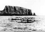 Native men in 10 bidarkas in open water with large rock formation in background.