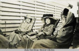 Three women in deck chairs.