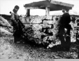 Two men standing by damaged pill box at Dutch Harbor.