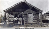 Man and woman on bench in front of log cabin.