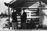 Two women standing in front of log cabin.