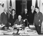 Governor Gruening (seated) signs the anti-discrimination act of 1945.