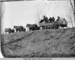 Six horses draw wagon along hillside.