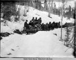 Horse-drawn sled with passengers and freight on snowy trails.