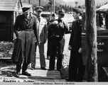 Five men, all in uniforms, on wooden sidewalk at Annette Island, Alaska, April 1942.