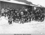 Large group of Barrow school children standing in front of school in the snow with Reverend...