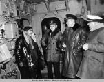 Mike Hodikoff, Aleut Chief, left; Commander Combs; Lieutenant Commander Anderson; unidentified...