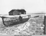Boy, possibly Harold Spriggs, seated inside wooden umiak frame laying on the snow.