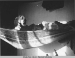 Rev. Spriggs son, Harold, sitting in a hammock.