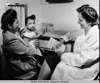 A nurse with an infant care booklet in hand speaking to a native mother holding a baby onboard the...