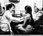 A nurse checks a girl's pulse with a stethoscope while a woman watches, onboard the vessel Hygiene.