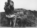 Samuel Spriggs with dog in front of sod house carrying large, unidentified item, possibly a piece...