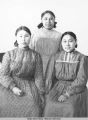 Three young Iñupiaq women wearing calico print western style dresses and hair ribbons pose for...
