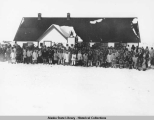 Church congregation or other large group of people outside white school building, possibly at...