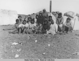 Group of Iñupiat posing in front of canvas tent in summer.