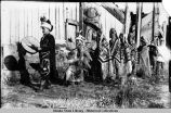 Haida Indians in ceremonial dress outside Dogfish house at Klinkwan, in row walking to left.
