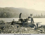 Men and dog with skiff on rocky beach.