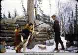 Betty, Agnes and Roger Huntington at the camp doing chores, i.e., cutting wood for cooking.