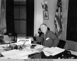 Ernest Gruening seated at desk, with telephone in hand.