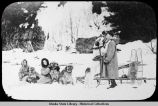 Man, woman, and child with dog team, sled, snowshoes.