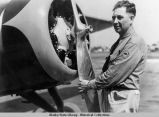 Sam O. White in game warden uniform, with hand on propeller.