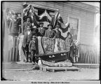Group of natives on porch, above coffin.