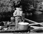 Man and washtub in skiff.