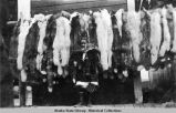 Young girl in parka standing below row of hanging pelts.