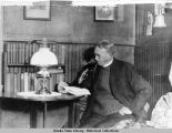 Bishop Rowe (?), seated at table, reading. Pt. Hope.