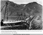 A section of the trans Alaska pipeline is lowered into a ditch in the Brooks Mountain Range, about...