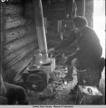 Ole Nichlai prepares supper in shelter cabin. Cantwell - Denali trail. 10/1941.