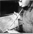 Eskimo school boy drilling ivory with primitive bow drill.  Little Diomede Island, 3/1942.