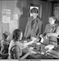 Postmaster Edna Chandler sells money order to student.  Eklutna Post Office, 11/1941.