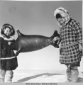 School girls exhibit seal poke, Hooper Bay, 3/1940.