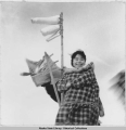 Schoolgirl hangs up laundry.  Whale esophagus dries on a pole.  Hooper Bay, 3/1940.