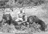 Hunter with rifle and two slain bears.