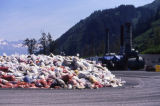 Large pile of bagged oily debris, incinerator.