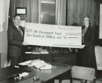 Governor Bill Sheffield holds a oversized check for $200,000,000 for the Alaska Permanent Fund,...