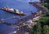 Aerial of omni-barge and spill workers hosing a beach.