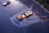 Workers hosing beach, barge trapping oil sheen.