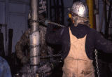 Oil laborer throws chain to tighten drilling pipe.