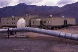 Shot of pipeline and barracks with satellite dish.