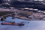 Aerial of oil holding tanks and oil tanker at terminal.