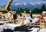 Workers double bag oily debris for added protection
