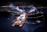 Maxi-barge and spill workers hosing beach, oil sheen escapes from containment boom.
