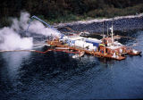 Aerial of a maxi-barge and spill workers hosing beach.