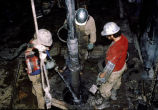 Oil laborers wash packing mud from drill pipe.