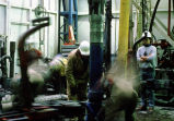 Oil laborers work drilling pipe with chain.
