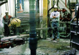 Oil laborers watch drilling pipe drill into oil well.